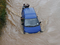 Gloucester, south west: Is it a van, or a boat? Passengers struggle through a flooded road on the outskirts of Gloucester.