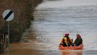Firemen in a rescue dingy sail down a flooded street with a local resident on the outskirts of Gloucester, western England (Reuters)