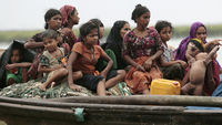 Rohingya refugees from Myanmar sit on a boat as they try to get into Bangladesh in Teknaf in June (Reuters)
