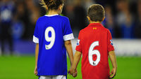 A boy and girl in Liverpool and Everton strips with the numbers 9 and 6 on the back (Getty)