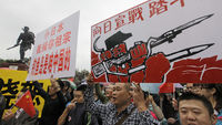 Chinese demonstrators hold signs and yell slogans during protest against Japan's decision to purchase disputed islands (Reuters)