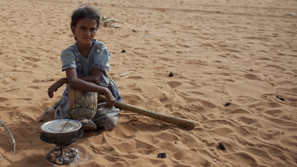 A young girl cooks rice in a refugee camp in Mauritania (picture: Reuters)