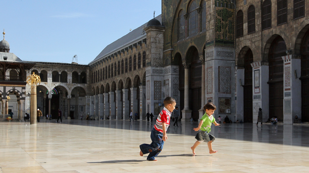 Children play outside the historic Umayyad Mosque in Damascus