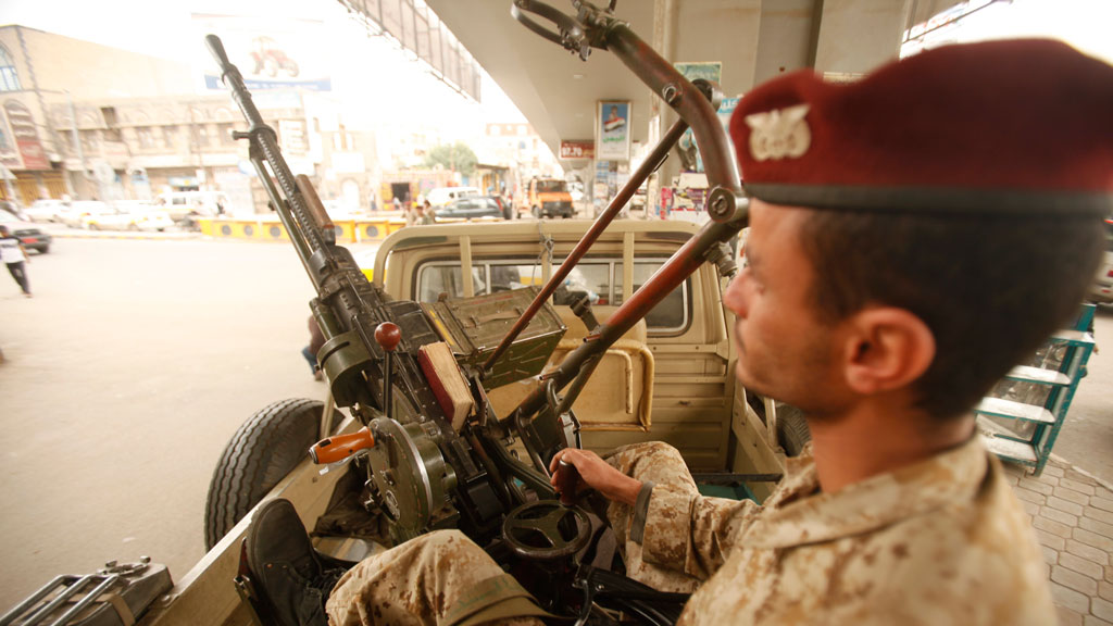 An army trooper sits beside a machinegun that is mounted on a patrol vehicle at at checkpoint in Sanaa (R)