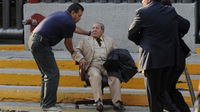 An elderly man is helped outside the Pemex building (Reuters)