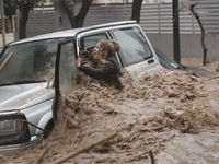 A woman shouts for help as she struggles to get out of her car that is rapidly being surrounded by rising flood water.