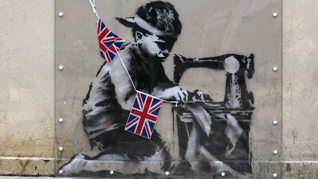 Slave Labour, which shows a young boy hunched over a sewing machine making Union flag bunting (Getty)