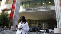 A member of the hospital staff walks in front of the Milstein Hospital Building at the NewYork-Presbyterian Hospital