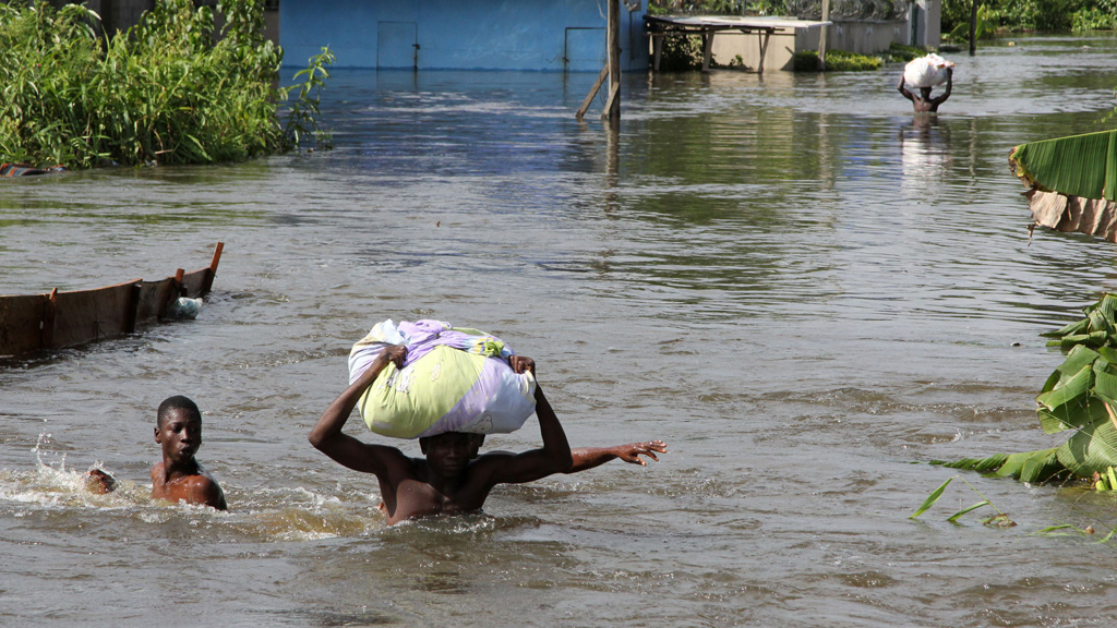 Victims of extreme rain flooding in Nigeria navigate the waters (picture: Reuters)