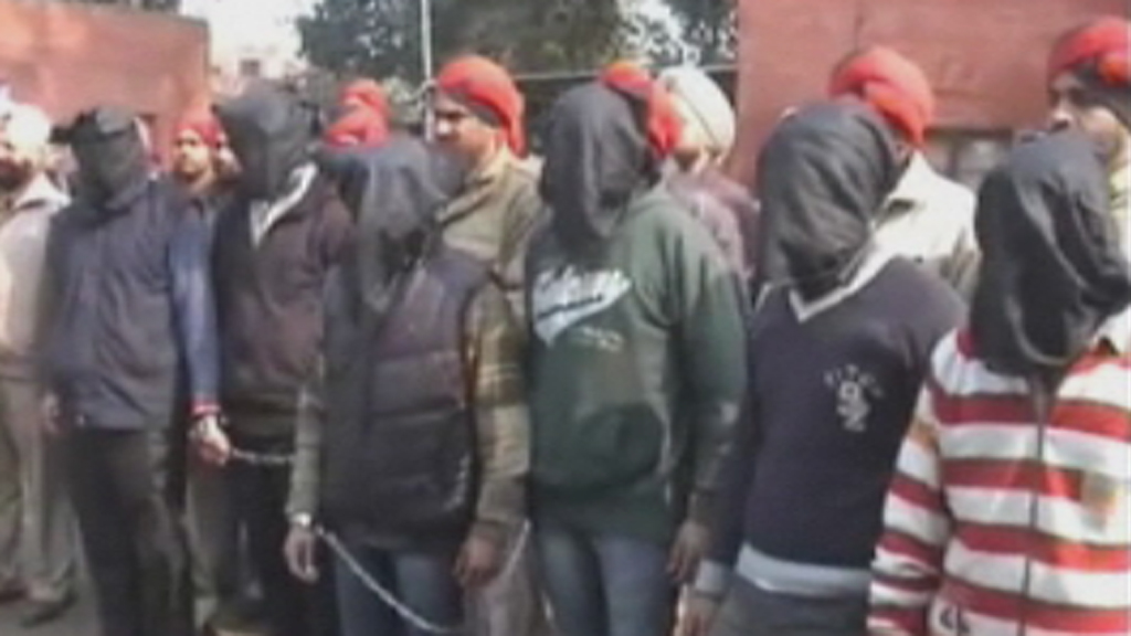 The suspects were shown hooded alongside Indian police