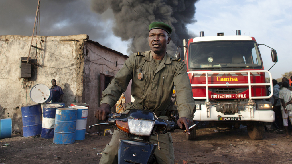A police officer rides a motorcycle after calling for help near fumes from a fire at Ngolonina market in the Malian capital of Bamako (Reuters)
