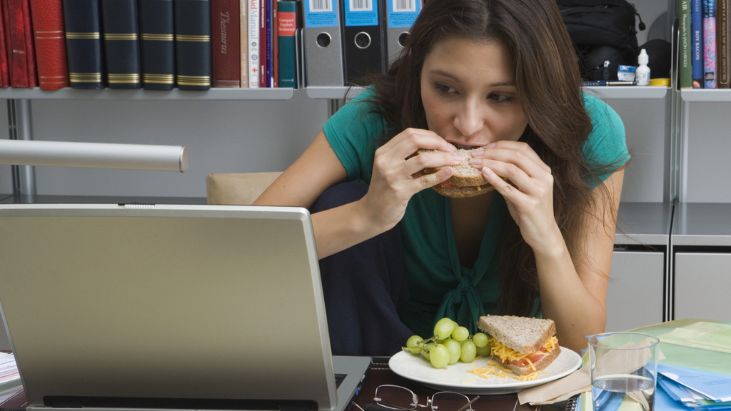 A woman eating at her desk (picture: Getty)