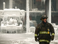 Chicago Fire Department Lieutenant De Jesus walks around the ice-covered warehouse that caught fire on the night of Tuesday 22 January.