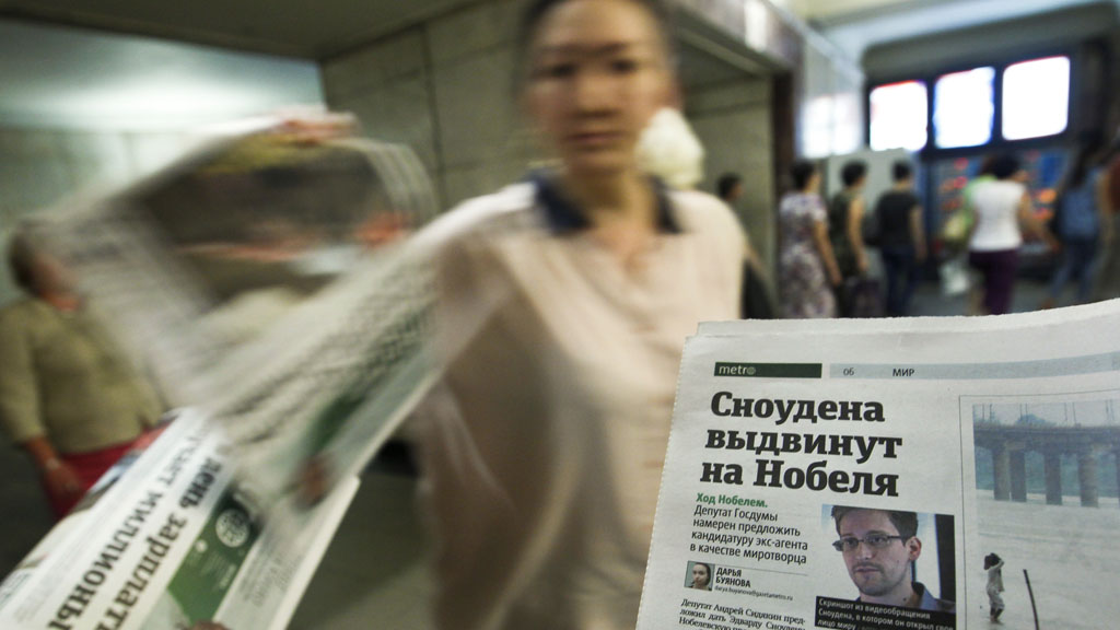 An employee distributes newspapers, with a photograph (R) of former U.S. spy agency contractor Edward Snowden
