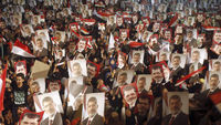 Muslim Brotherhood holds up Mohammed Morsi pictures (R)