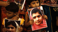 Children hold portraits of Malala Yousufzai in Karachi on the day declared Malala Day by the UN (R)