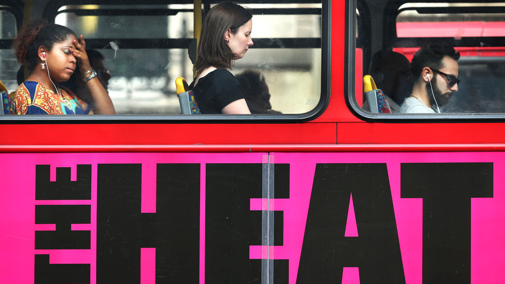 Passengers travel on a bus with The Heat advertisement (G)
