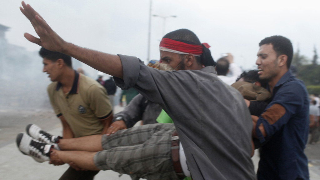 Supporters of deposed Egyptian President Mohammed Morsi carry a protester injured during clashes. (Reuters)