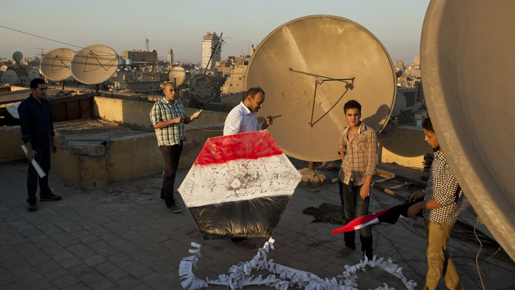 Supporters of the Egyptian Army prepare to fly a kite painted in the colours of the Egyptian flag from a rooftop during a demonstration at Tahrir Square. (Reuters)