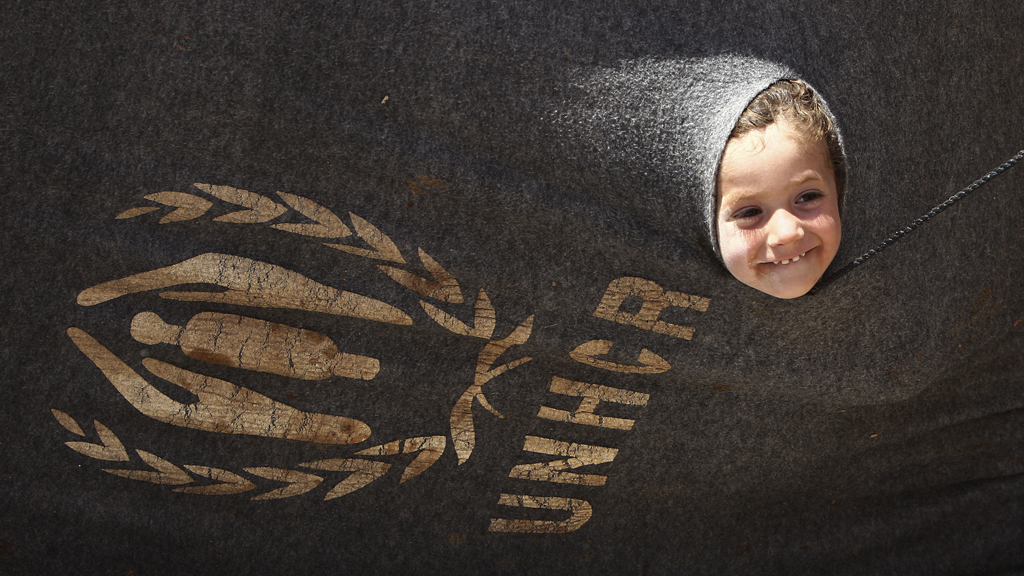 Refugee child from Syria looks out from a UNHCR tent. (Reuters)