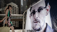 A woman walks past a banner displayed in support of former US spy Edward Snowden in Hong Kong (Getty)