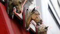 Plastic horses heads decorate the frontage of a French butcher shop (G)