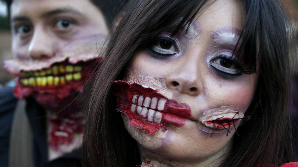 People wear make-up and dress up to take part in a zombie march (R)