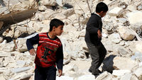 Syrian children walk past destroyed buildings in the northern city of Aleppo on March 24 (Getty)