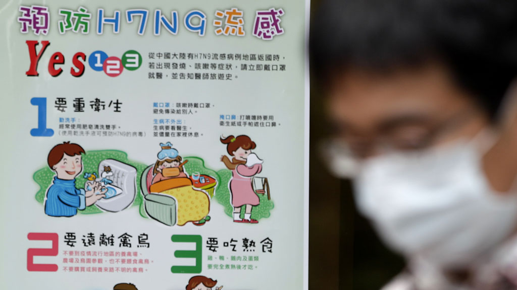 A man wearing a medical mask walks in front of a poster about the prevention of H7N9 bird flu virus (pic: Reuters)