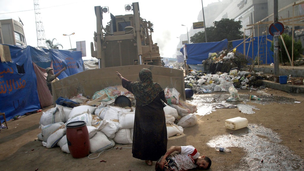 In Egypt a woman stands between a bulldozer and an injured protester the army cracked down on pro-Morsi demonstrators in August (G/R)