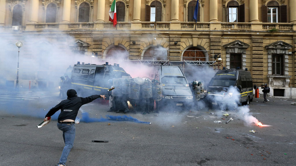 In October a demonstrator throws a bottle at the Guardia di Finanza during a protest in Rome as tensions rise over unemployment (G/R)