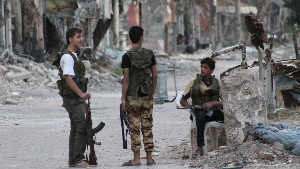 Rebel fighters secure an heavily damaged street in Syria's eastern town of Deir Ezzor (G)