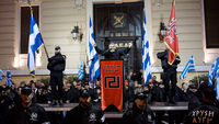 Members of the extreme-right Golden Dawn party stand around a stage while the leader of the party Nikolaos Mihaloliakos delivers a speech on February 2, 2013 in Athens, Greece.