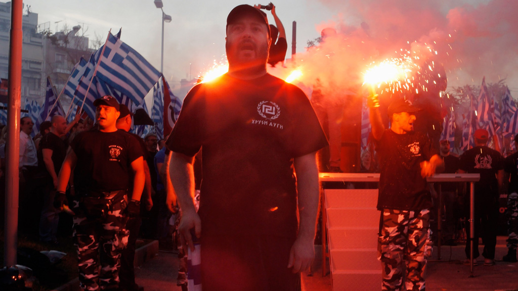 Members of the extreme-right Golden Dawn party stand around a stage and chant the National anthem during a gathering on May 26, 2013 in Athens, Greece.
