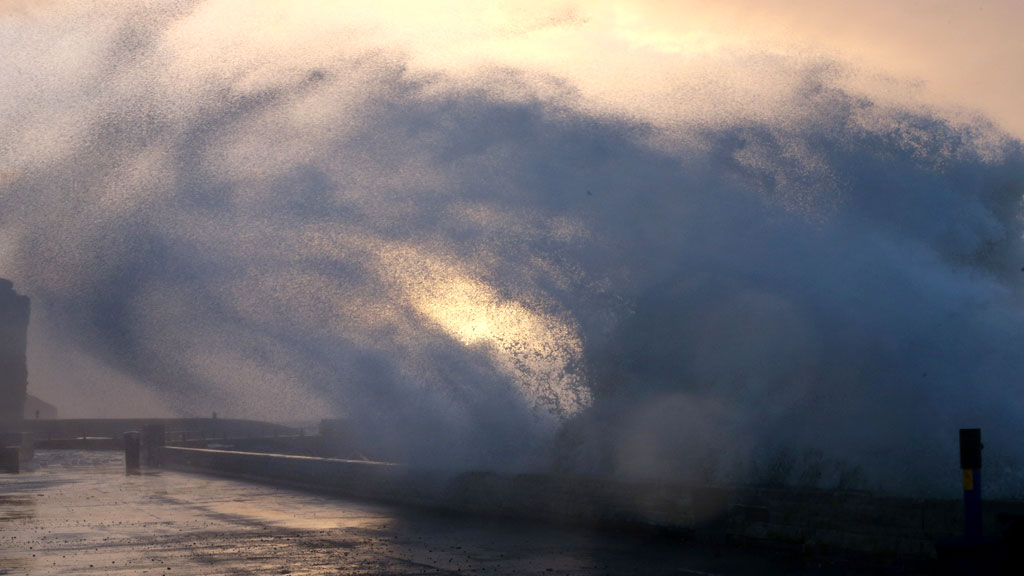 A wave breaks over the seafront at dawn in West Bay, Dorset (G)