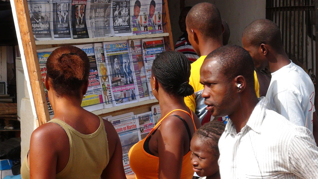 Conakry residents scan headlines (Reuters)