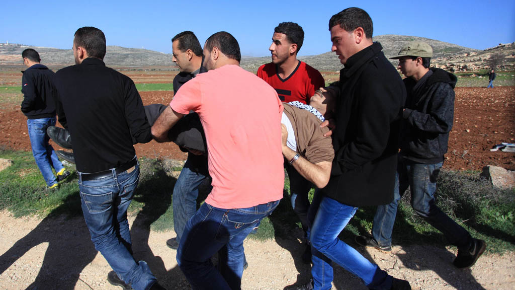 Ziad Abu Ein is carried away by protesters after collapsing