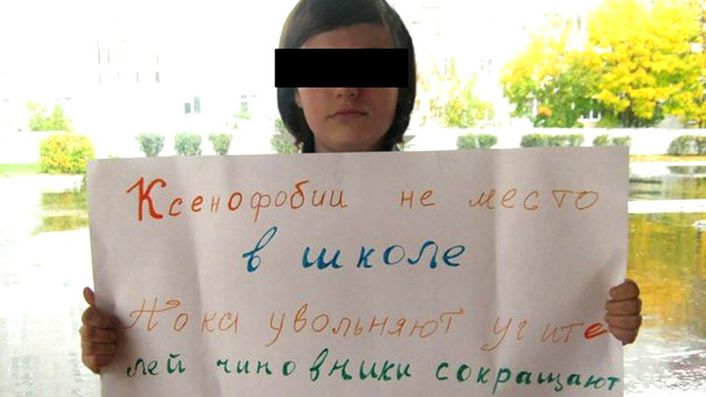 Maria Novikova holds a banner which says 'There is not place for xenophobia in schools. While teachers are sacked, bureaucrats cut the budgets'