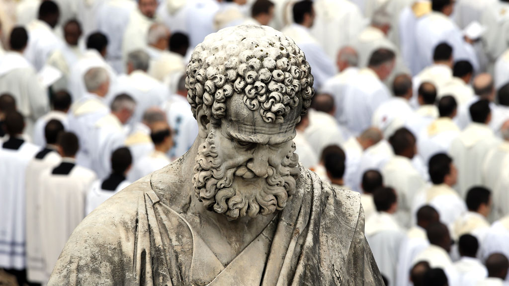A mass takes place behind St Peter's statue, in the Vatican City's St Peter's Square (R)