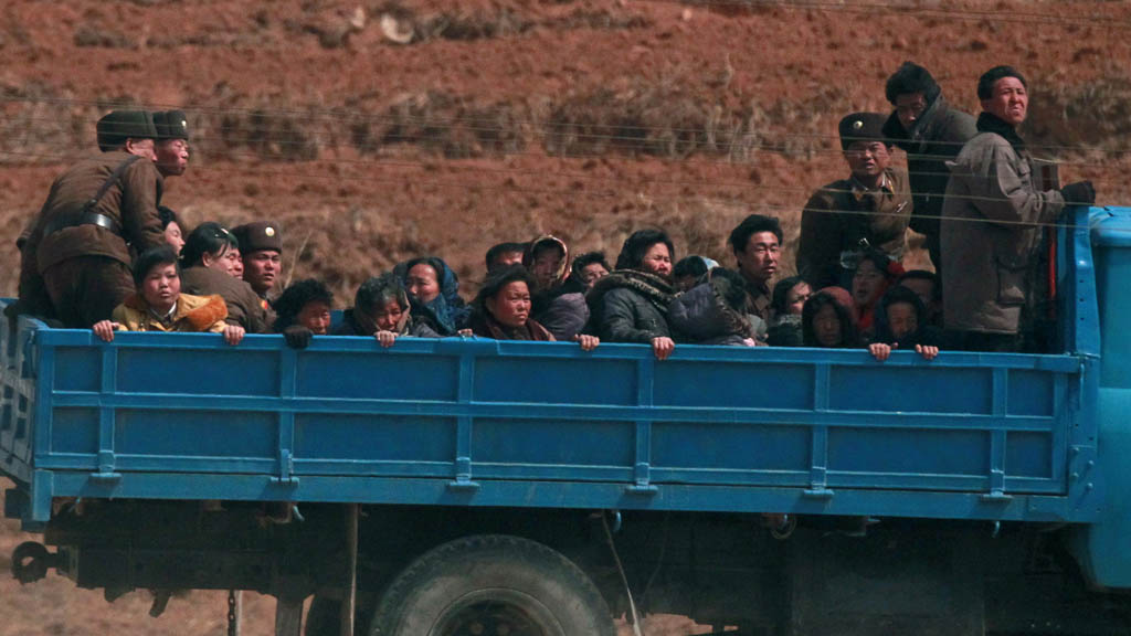 Villagers travel in a truck in a field northwest of Pyongyang