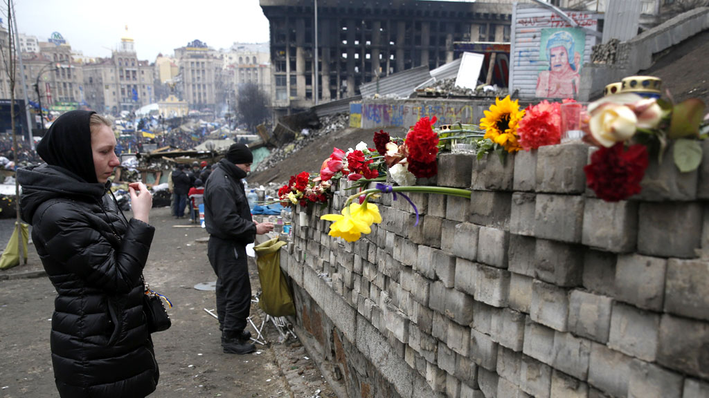 A woman makes the sign of the cross in front of a flower covered wall in Independence Square, Kiev.