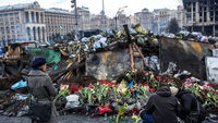 People place flowers at a memorial to anti-government protesters killed in chashes with police (G)