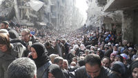 Thousands of hungry, trapped residents of Yarmouk in Syria queue for food aid (Reuters)
