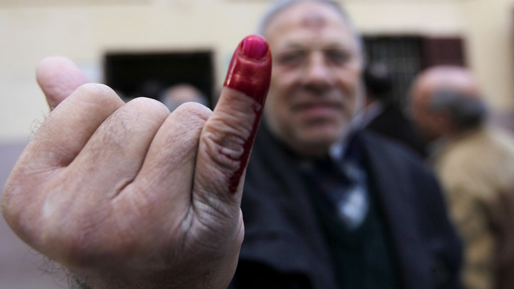 Egypt referendum: voter holds up ink stained finger aftering oting at polling station in Cairo (picture: Reuters)