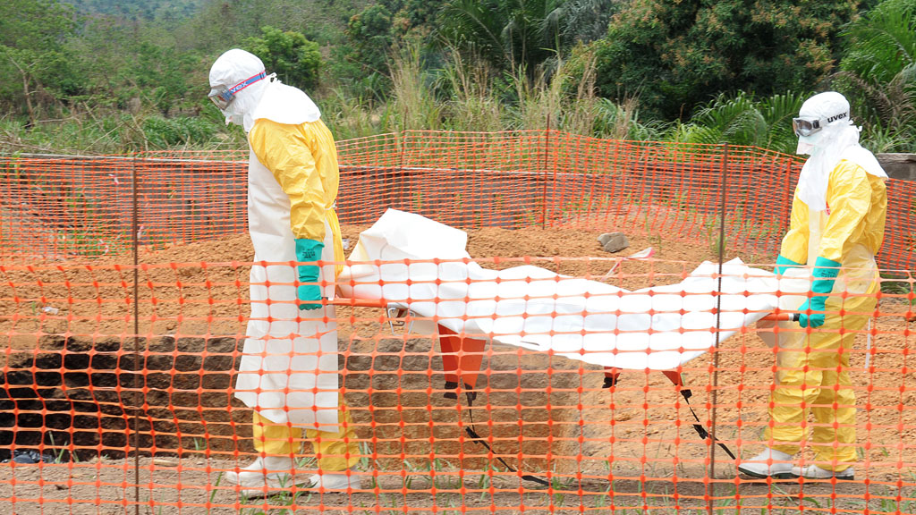 Doctors in protective gear move the body of an Ebola victim (Getty)