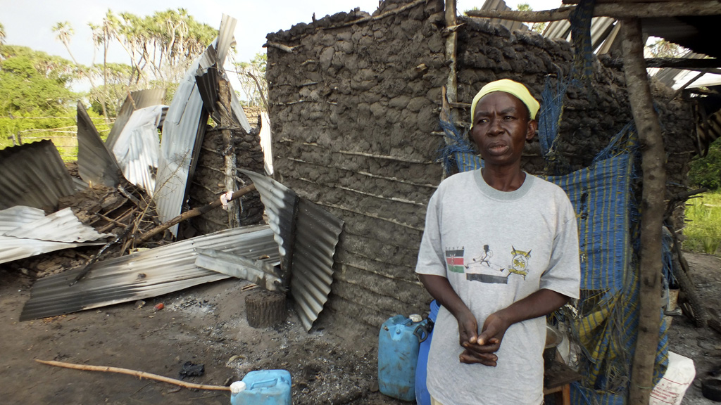A woman stands outside a partly destroyed house after gunmen attacked Hindi village