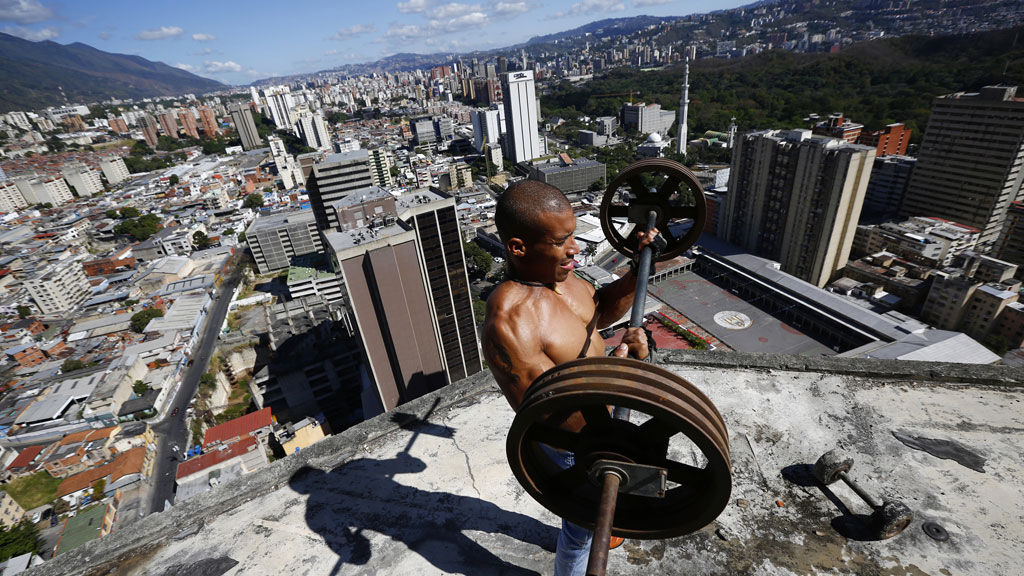 Gabriel Rivas, 30, lifts weights on a balcony on the 28th floor of the