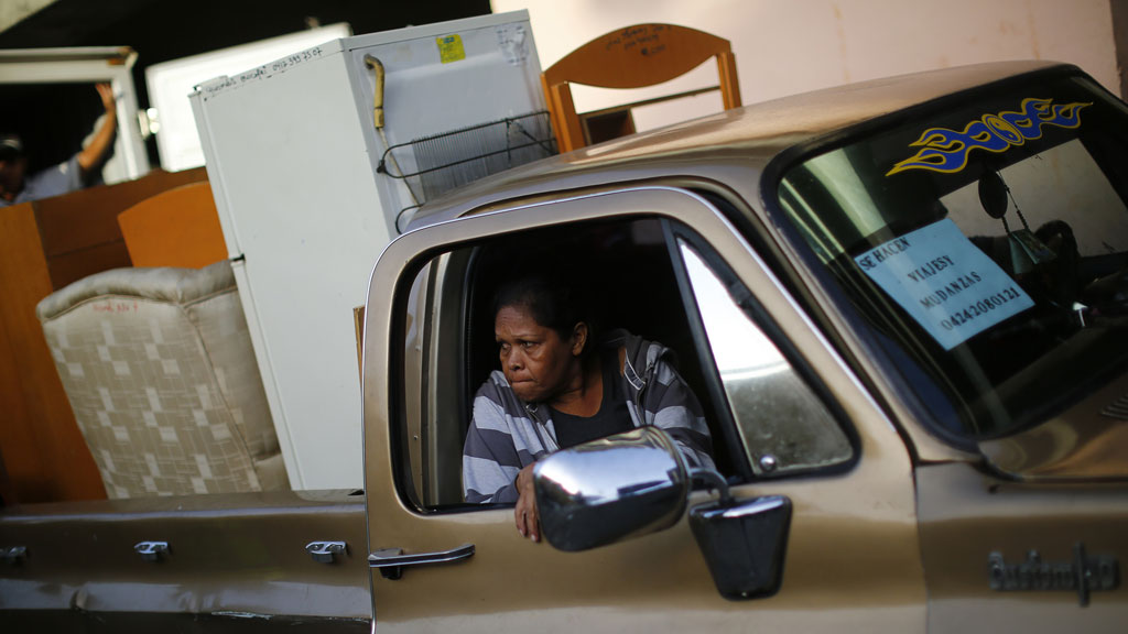 An evicted resident of Tower of David sits in a pick-up truck