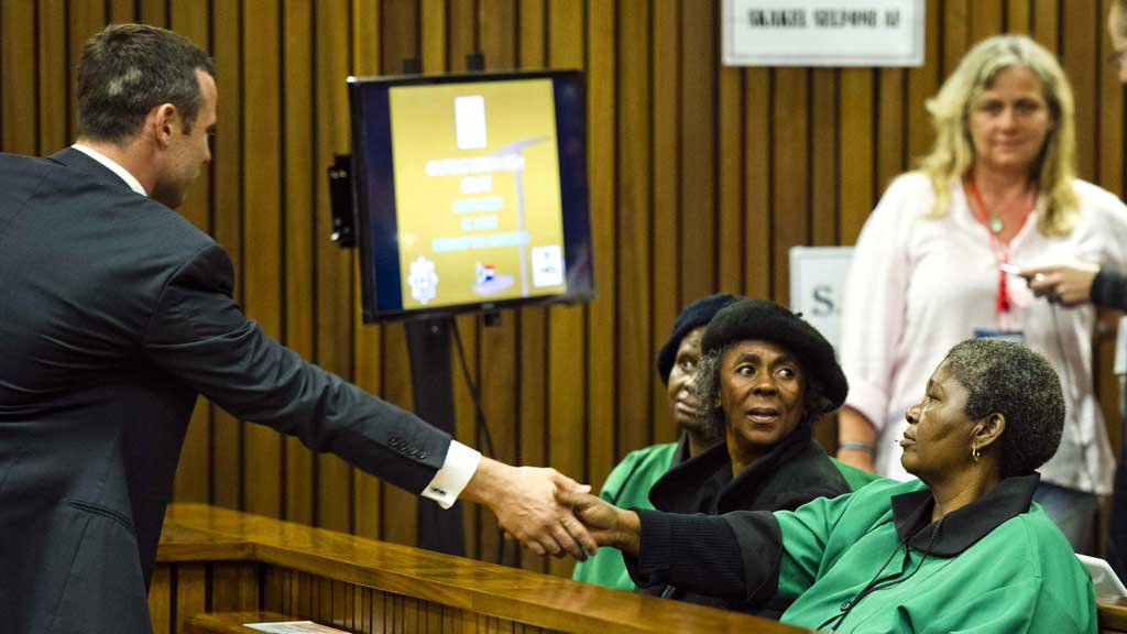 Oscar Pistorius greets members of the African National Congress Women's League during the fifth day of his trial (R)