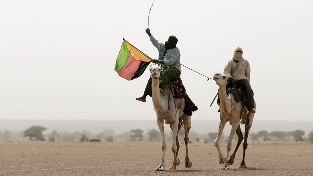 A Tuareg man holds the MLNA flag in July 2013